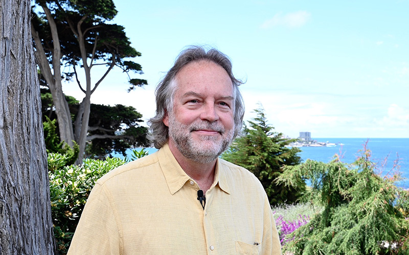 Portrait of a man in a yellow shirt near a tree; the ocean is seen in the background