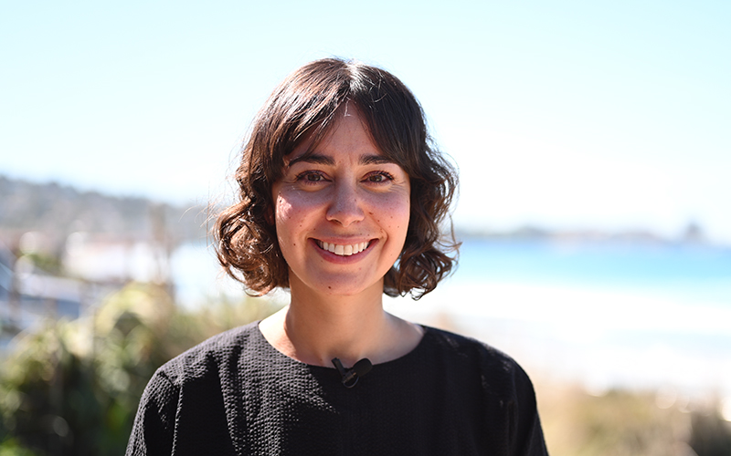 Portrait of a smiling woman with short brown hair, a beach is visible in the background