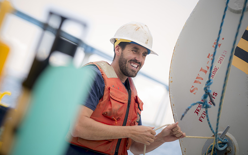 An oceanographer wearing a safety hat and life jacket conducts research on a ship