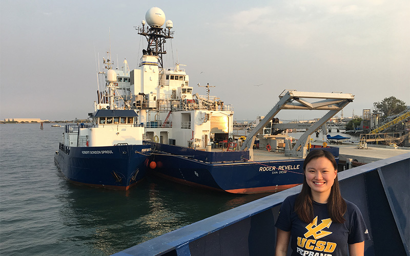 A young woman in a UCSD t-shirt stands in front of a docked ship.