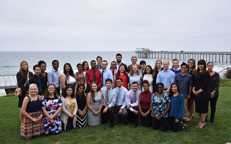 Group photo of students gathered on a lawn near the ocean.
