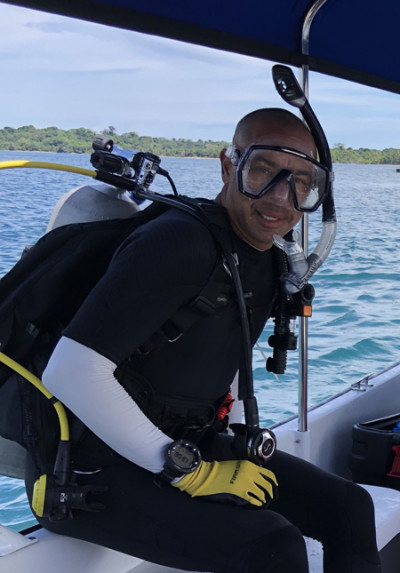A man in scuba diving gear sits on the edge of a boat