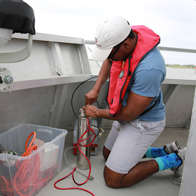 A student on a research vessel fills a small vial with water