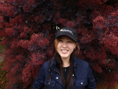 A smiling woman in a baseball cap stands in front of a large plant with pink flowers