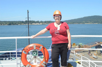 A woman in a hard hat and red shirt stands on a boat