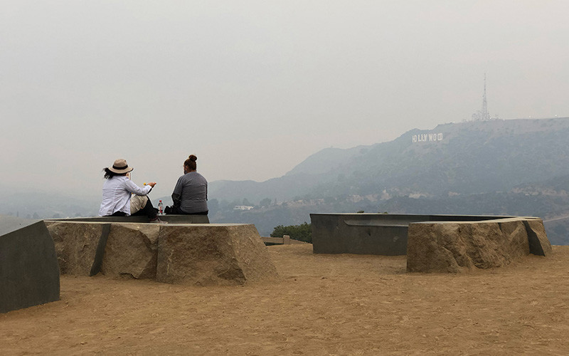 Two people sitting on a bench in smoky air overlooking Hollywood sign.