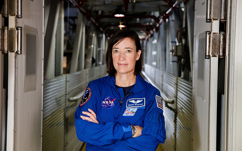 Portarit of a female astronaut with short brown hair wearing a blue jumpsuit. She is standing in a training facility and her arms are crossed.