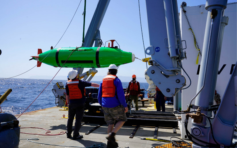 Crew members launch an AUV off a research vessel