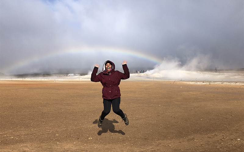 A woman jumps in an outdoor setting in Iceland near a rainbow