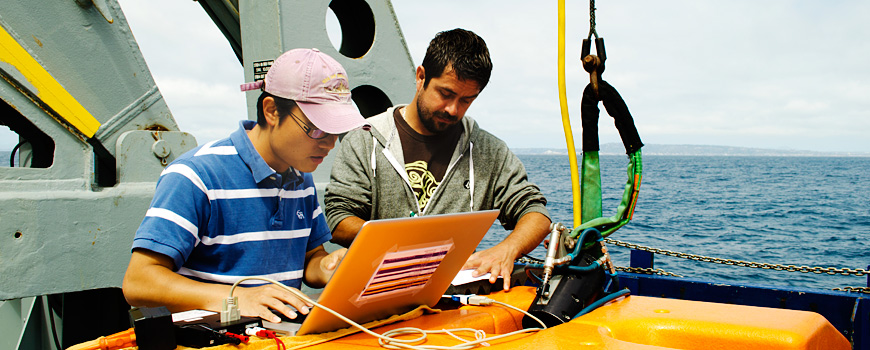 Two students working aboard a ship at sea.
