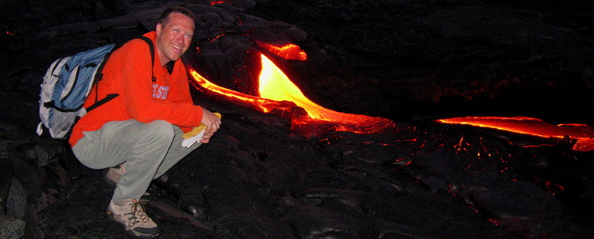 Man crouched next to flowing lava.