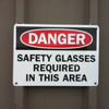 Sign reading Danger, safety glasses required in this area