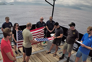 Flag ceremony to honor American MIAs held above the wreckage of a Grumman TBF Avenger lost in World War II offshore Hawaii. Photo: Kyle McBurnie
