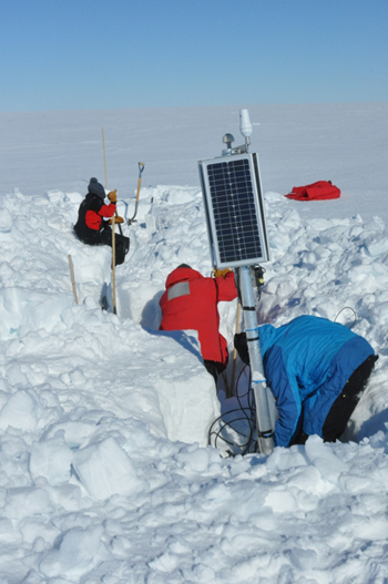 Scientists dig a seismometer out of the ice.