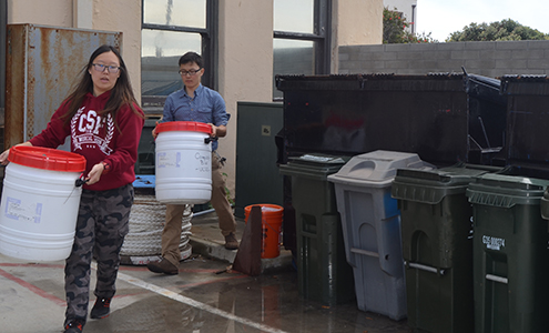 Student interns Will Tanaka and Candice Chung collect compost bins from the Scripps campus