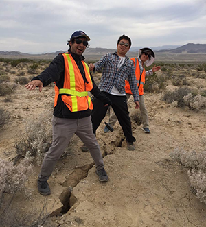Scripps Oceanography geoscientists Ignacio Sepulveda, Xiaohua Xu, and Jennifer Haase straddle a fault offset that formed in Ridgecrest, Calif., following the magnitude 6.4 earthquake that struck in July. Before the earthquake, their feet would have been next to each other, illustrating the significant left-lateral ground rupturing that occurred.