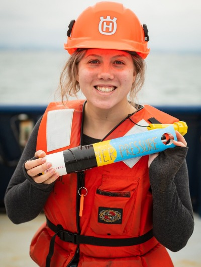 A woman on a research vessel holds a small instrument.