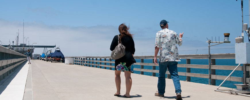 People visit Scripps Pier during a tour