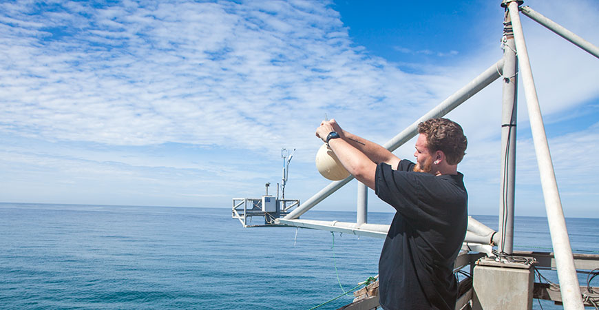 Shane Clark of the Keeling lab at Scripps Institution of Oceanography collects an air sample at the end of Scripps Pier.