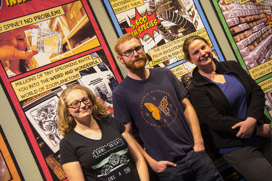 Three scientists in front of comic panels.
