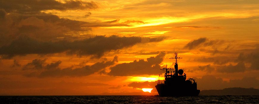Ship silhouetted against a golden sunset.