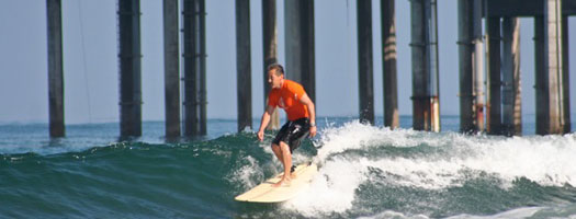 Surfer in front of Scripps Pier pilings