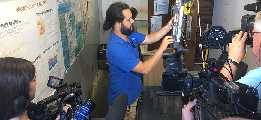 News media members film seawater temperature measurements at Scripps Pier, Aug. 2, 2018