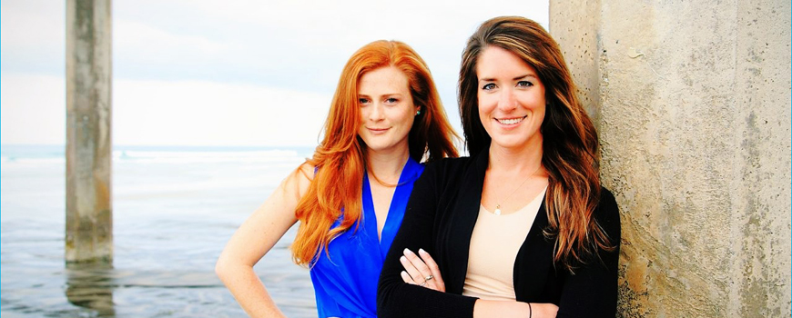 Two women stand by a pier.