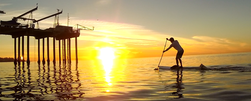 A stand-up paddleboarder in the water at sunset