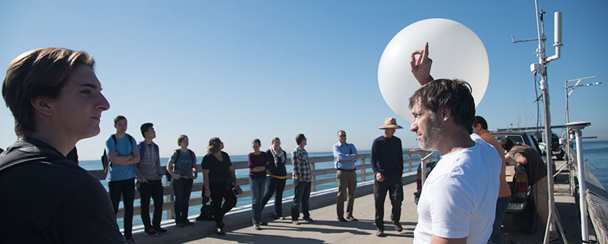 Amato Evan points skyward with a weather balloon in the background.