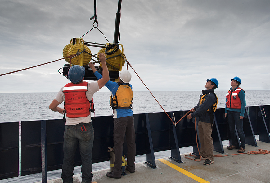 Assistant research oceanographer Ana Širović (right) watches  as crewmembers recover an acoustics package