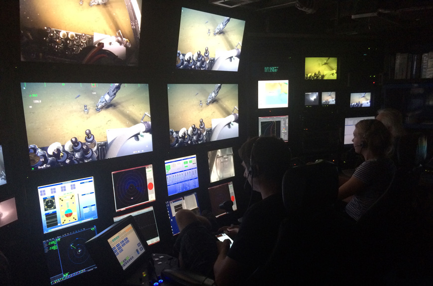 Two scientists look at multiple screens showing deep-sea video footage being filmed by a remote operated vehicle.