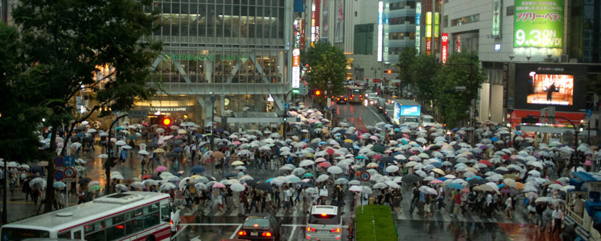 Hundreds of people carrying umbrellas cross an intersection in Japan.
