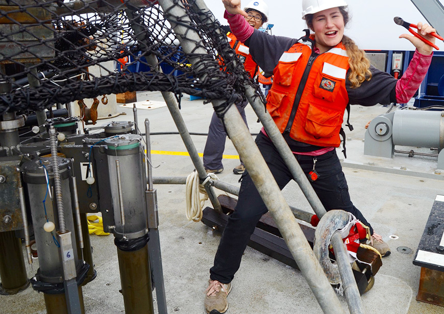 Female scientist celebrating on board a ship. Photo by Melissa Miller.