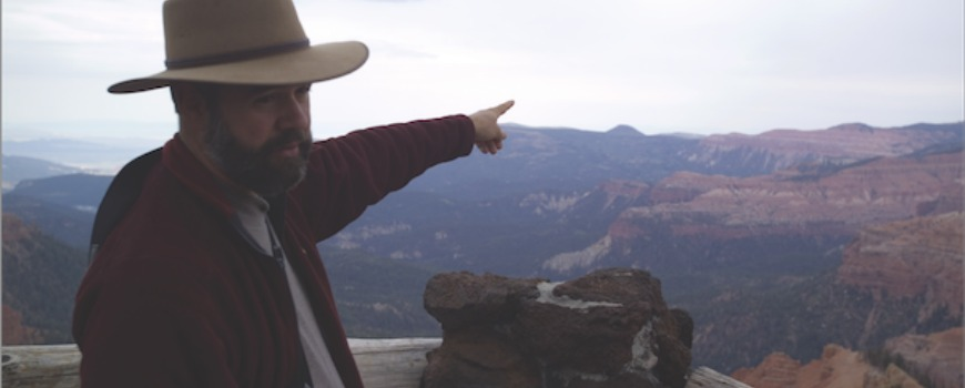A man points at mountains.