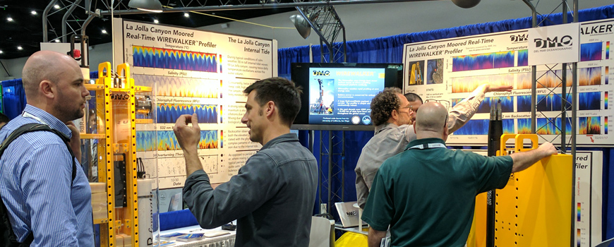 Scripps scientists and colleagues visit Del Mar Oceanographic's Wirewalker exhibit at the 2018 OiA conference.