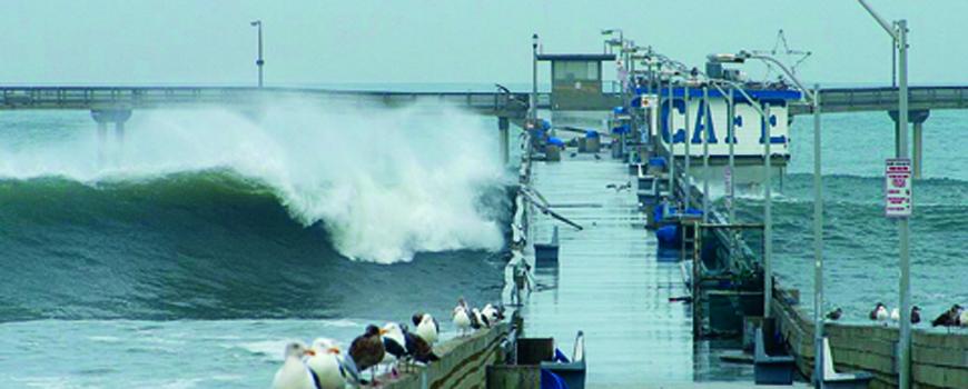 waves crashing over a pier