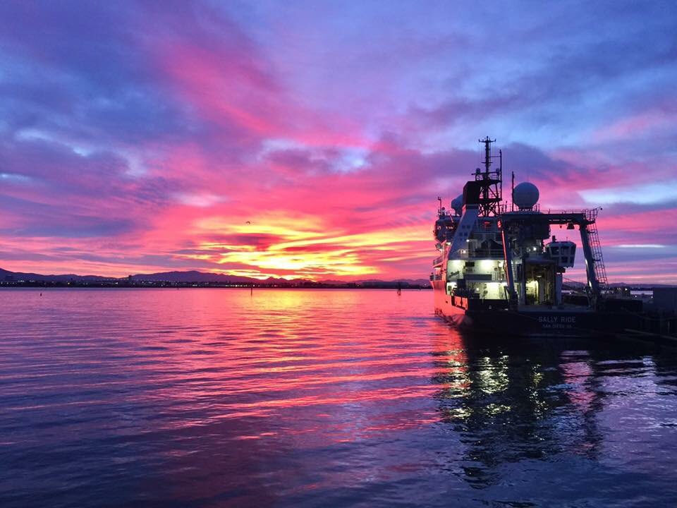 Research vessel Sally Ride at dock in front of orange, red and purple sunset
