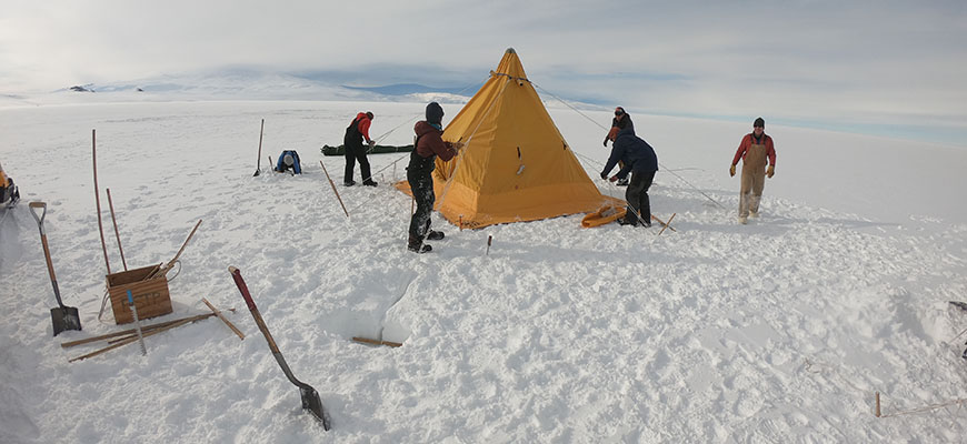 During a field training course in Antarctica, members of the team secure a tent. Photo by Jacob Morgan.