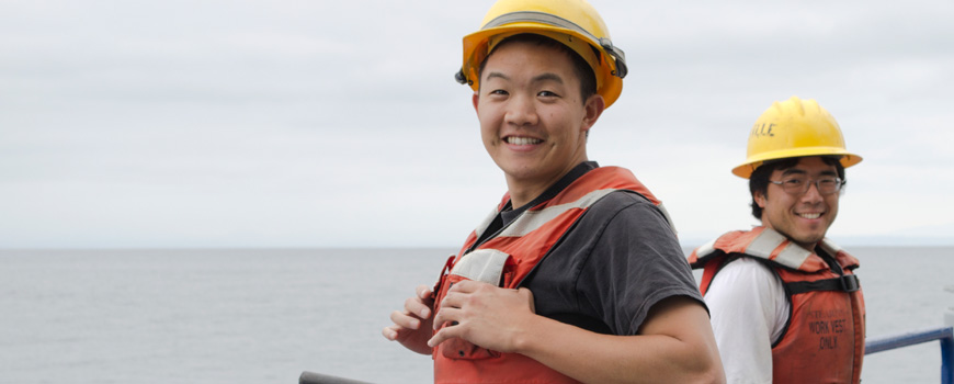 Student aboard ship in safety vest and helmet.