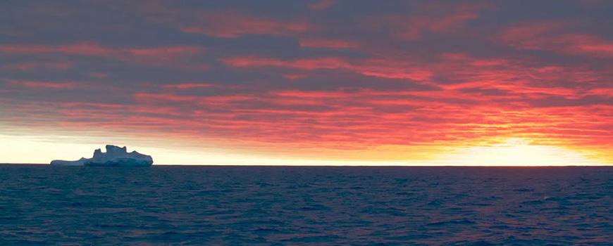 Iceberg silhouetted against sunrise