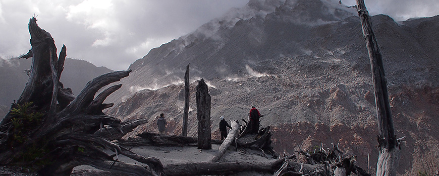 Two men looking across ashy terrain at smoldering volcano.