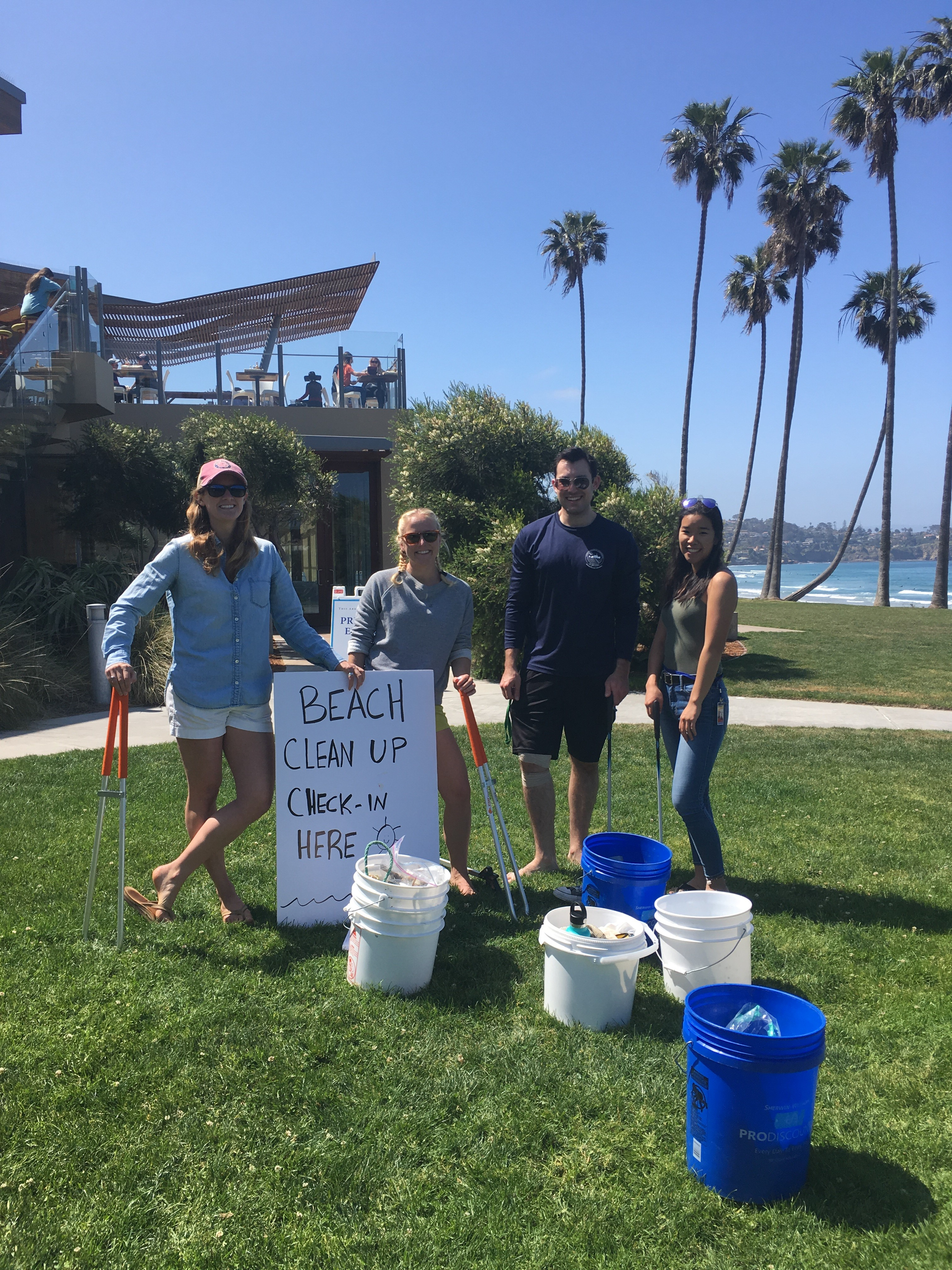 Scripps students and staff pose with the buckets of trash they collected on the beach as part of Earth Week