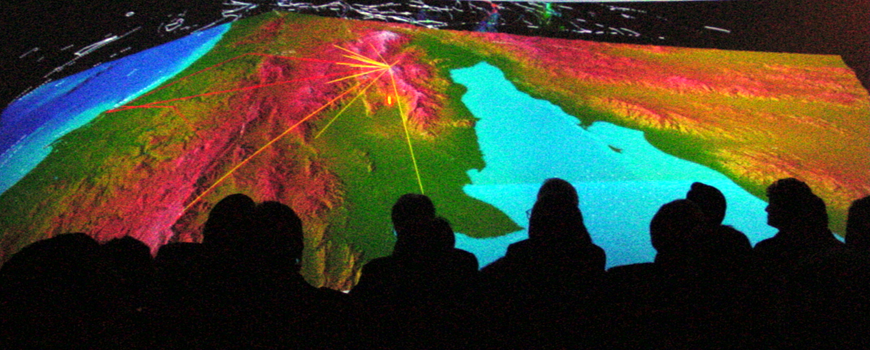 Audience members are silhouetted against a data display.