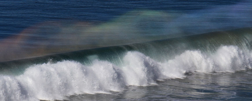 Multicolored light shimmers through the spray of a wave crashing on shore.