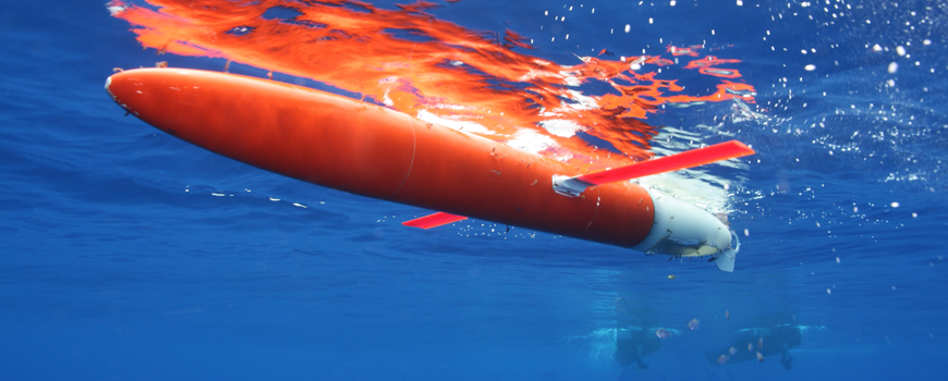 A brightly colored propellor-less glider sits in clear blue water.