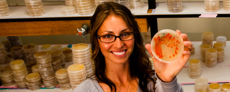 A smiling woman in a laboratory holds a petri dish with growth on it.