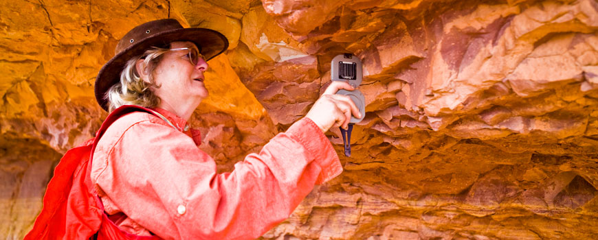 Professor Lisa Tauxe uses a handheld device to check the magnetic field of a rock formation.