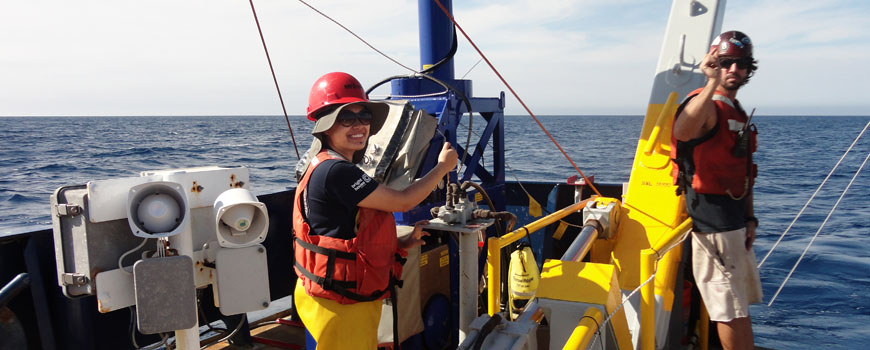 A young woman conducts research aboard an oceanographic research vessel.