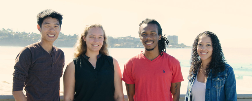 Four grad students smile with the ocean behind them.